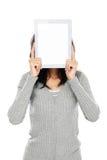 Frau, die ihr Gesicht mit Tablet-Computer bedeckt stockbilder