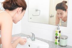Frau, die ihr Gesicht mit Wasser über Badezimmerwanne wäscht Lizenzfreie Stockbilder