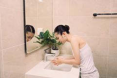 Frau, die ihr Gesicht mit Wasser über Badezimmerwanne wäscht Stockfotos
