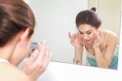 Frau, die ihr Gesicht mit Wasser über Badezimmerwanne wäscht Stockbilder