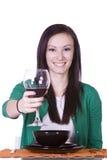 Frau, die ihr Getränk zur Kamera anhebt Stockbild
