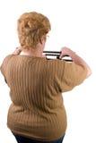 Frau, die ihr Gewicht auf Skala überprüft Stockfoto