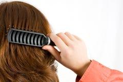 Frau, die ihr Haar aufträgt Stockbild