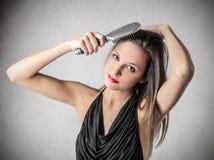 Frau, die ihr Haar bürstet Lizenzfreie Stockbilder