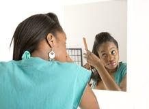 Frau, die ihr Haar im Spiegel tut lizenzfreie stockfotografie