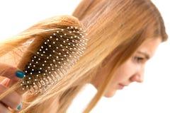 Frau, die ihr Haar kämmt Stockfotografie