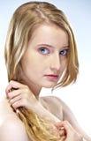 Frau, die ihr Haar zieht lizenzfreies stockbild