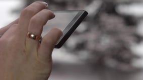 Frau, die ihr intelligentes Mobiltelefon im Winter im Freien verwendet stock video