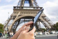 Frau, die ihr intelligentes Telefon vor Eiffelturm verwendet Stockfotos
