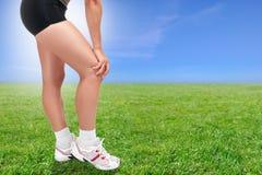Frau, die ihr Knie hält stockfoto