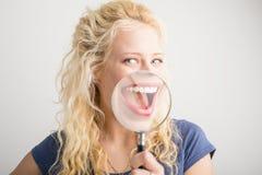 Frau, die ihr Lächeln durch Lupe zeigt Stockfotografie