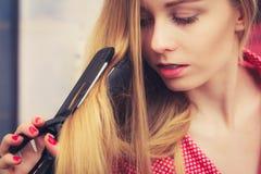 Frau, die ihr langes blondes Haar geraderichtet Stockbild