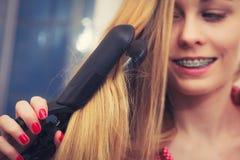 Frau, die ihr langes blondes Haar geraderichtet Lizenzfreies Stockbild