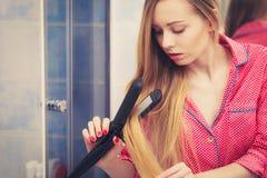 Frau, die ihr langes blondes Haar geraderichtet Stockfotografie