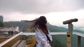 Frau, die ihr langes Haar auf Höchst-Hong Kong spinnt stock footage