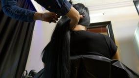 Frau, die ihr langes Haar gebürstet am Schönheitswohnzimmer erhält stock video footage