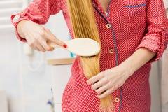 Frau, die ihr langes Haar im Badezimmer bürstet Stockbilder