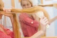 Frau, die ihr langes Haar im Badezimmer bürstet Lizenzfreie Stockbilder