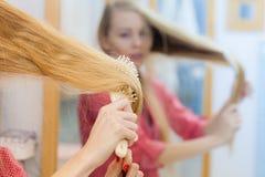 Frau, die ihr langes Haar im Badezimmer bürstet Stockfotografie