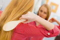 Frau, die ihr langes Haar im Badezimmer bürstet Lizenzfreies Stockfoto