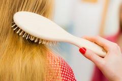 Frau, die ihr langes Haar im Badezimmer bürstet Lizenzfreie Stockfotografie