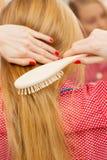 Frau, die ihr langes Haar im Badezimmer bürstet Lizenzfreies Stockbild