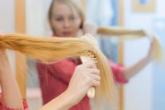 Frau, die ihr langes Haar im Badezimmer bürstet Stockfotos