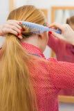 Frau, die ihr langes Haar im Badezimmer kämmt Lizenzfreies Stockfoto