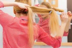 Frau, die ihr langes Haar im Badezimmer kämmt Lizenzfreie Stockfotografie