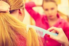 Frau, die ihr langes Haar im Badezimmer kämmt Stockfotos