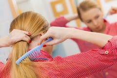 Frau, die ihr langes Haar im Badezimmer kämmt Lizenzfreies Stockbild