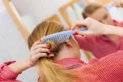 Frau, die ihr langes Haar im Badezimmer kämmt Stockbilder