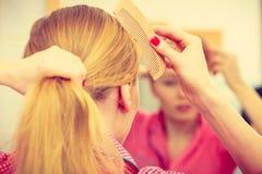 Frau, die ihr langes Haar im Badezimmer kämmt Stockbild