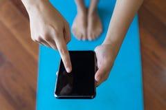 Frau, die ihr Telefon Appprogramm für Yogaübung verwendet stockbilder