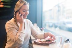 Frau, die ihr Telefon in der Zugkabine verwendet, um mit Freunden zu sprechen Stockbild