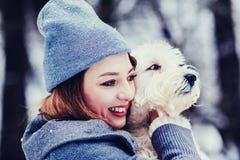 Frau, die ihr weißes Hündchen des Haustieres streichelt lizenzfreies stockfoto