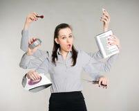 Frau, die ihre Arbeit mehrere Dinge gleichzeitig tut Lizenzfreie Stockfotos