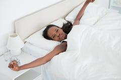 Frau, die ihre Arme beim Aufwachen ausdehnt stockbild