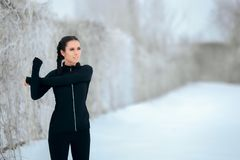 Frau, die ihre Arme bereit, im Freien in der Wintersaison auszuüben ausdehnt stockbilder