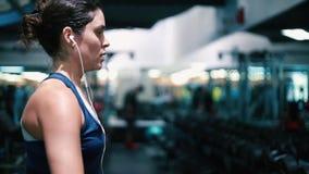 Frau, die ihre Arme an der Turnhalle mit Gewichten ausarbeitet stock video footage