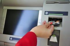 Frau, die ihre ATM-Karte in ATM setzt Lizenzfreie Stockfotografie