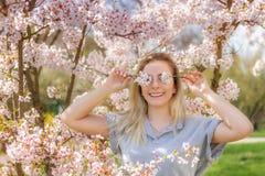 Frau, die ihre Augen mit frischen bunten Blumen bedeckt Stockfotografie