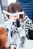 Frau, die ihre Augen von einem Augendoktor überprüfen lässt Stockfoto