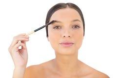 Frau, die ihre Augenbraue bürstet Stockbilder