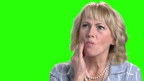 Frau, die ihre Backe wegen der Zahnschmerzen berührt stock video footage
