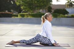 Frau, die ihre Beine auf einer Yogamatte ausdehnt Stockfoto
