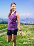 Frau, die ihre Beine bevor dem Laufen ausdehnt Lizenzfreie Stockfotografie