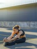 Frau, die ihre Beine in der Stadt ausdehnt Stockbilder