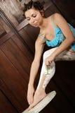 Frau, die ihre Beine rasiert Stockfotografie