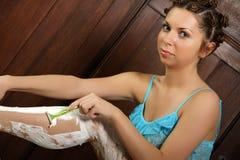 Frau, die ihre Beine rasiert Stockbilder
